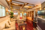 Large TV room with custom built-ins and skylights, opens to outdoor patio